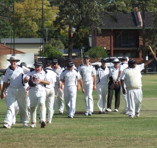 Matchwinning batsman Channa DeSilva waves a stump to the crowd, as the triumphant team comes off with umpire Brian Lazzaro, led by coach Rex Bennett and keeper Peter Golding on the left.