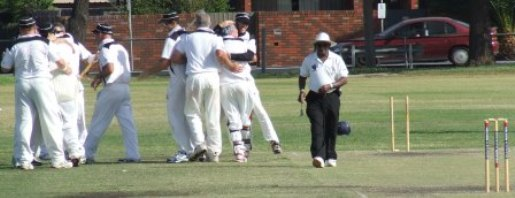 The players are ecstatic at the fall of Maribyrnong Park's final wicket, as umpire Lucky Mendis walks down the pitch.