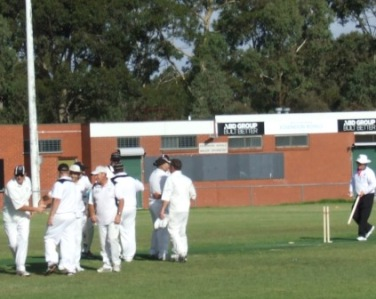 The players are all in together for the Premiership huddle, as umpire Peter Gould returns the cartwheeled stump.