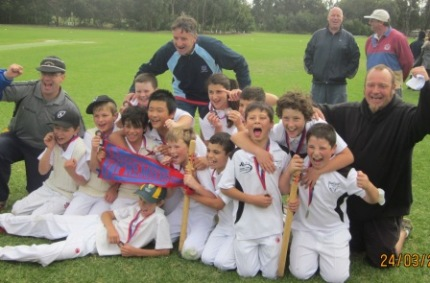 The Under 12 team with their 2011/12 flag and medals. Coach Paul Baks (right) is joined by assistant coaches Michael Cumbo (left) and Bill Blair, while Moonee Valley legends Warwick Nolan and Tony Hicks stand in the background.